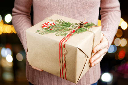 Woman hands holding gift box wrapped in kraft paper, tied with twine and decorated with a juniper branch and candy. Archivio Fotografico