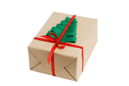 Gift box wrapped in kraft paper, tied with red ribbon and decorated with a green ribbon in the shape of a Christmas tree. Isolated on white. Archivio Fotografico