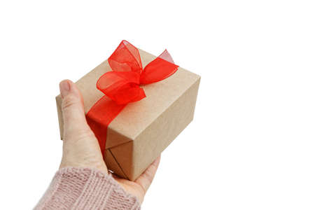 Woman hands holding gift box wrapped in kraft paper with red bow isolated on white background