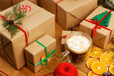 Group of christmas gift boxes wrapped in kraft paper, tied with twine and cup of coffee with marshmallow on wooden table.