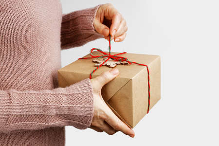 Female hands holding gift box wrapped in kraft paper and tied with twine against gray background. Copyspace