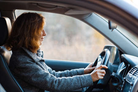 Portrait of a redhead woman driving a car and looking straight ahead. Archivio Fotografico