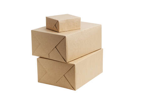 Closed brown cardboard boxes wrapped in kraft paper without label. Box for parcel, delivery or packaging isolated on white background.