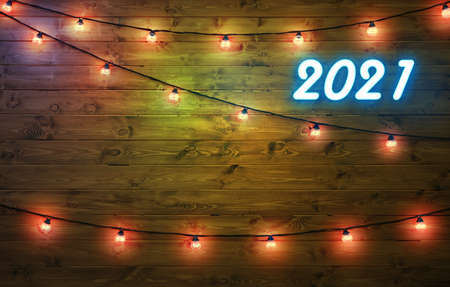 2021 happy new year background. Neon numbers 2021 and garlands with lights on wooden background. Copyspace.