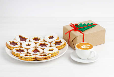 Cup of coffee, homemade cookies and gift box wrapped in kraft paper decorated with a green ribbon in the shape of a Christmas tree on white wooden table. Copyspace.