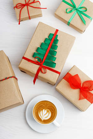 Group of gift boxes wrapped in kraft paper, tied with twine and decorated with a ribbons on white wooden table. Archivio Fotografico