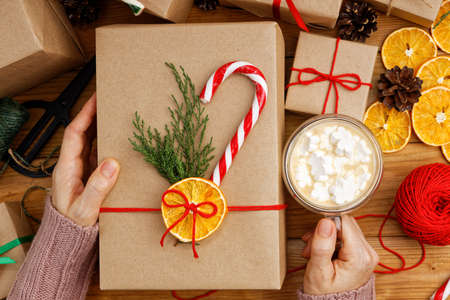 Female hands holding gift box wrapped in kraft paper and tied with twine and cup of coffee with marshmallow. Top view.