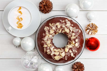 Homemade chocolate cheesecake with almond slices, cup of coffee cappuccino and Christmas balls on white wooden table. Top view.