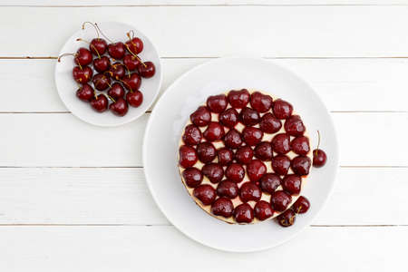 Homemade cake with cherries on white wooden table. Top view. 스톡 콘텐츠