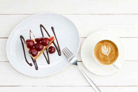 Closeup piece of homemade cake with cherries and cup of coffee cappuccino on white wooden table. Top view.