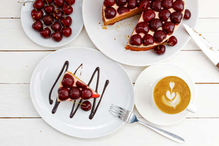 Closeup homemade cake with cherries and cup of coffee cappuccino on white wooden table. Top view.