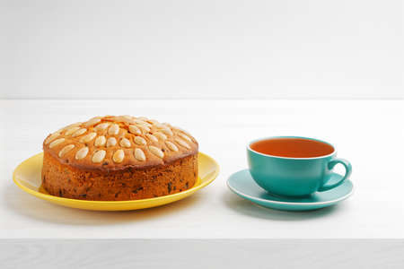 Homemade cake with almonds and cup of tea on a white wooden table. Copyspace.