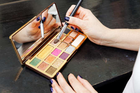 Closeup palette of an eye shadows and womans hand with brush. Shallow focus. 스톡 콘텐츠