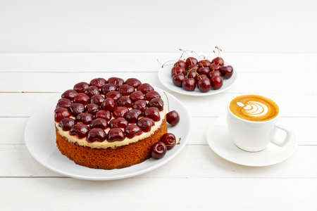 Homemade cake with cherries and cup of coffee cappuccino on white wooden table. Shallow focus. 스톡 콘텐츠