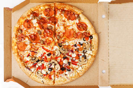 Half meat and half vegetable pizza in open cardboard box. Top view.