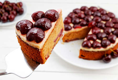 Closeup piece of homemade cake with cherries against blurred background of table. Shallow focus