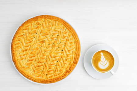 Homemade gooseberry lemon pie and cup of coffee cappuccino on white wooden table. Top view.
