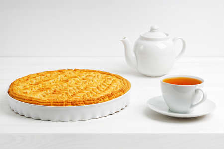 Homemade gooseberry lemon pie and cup of tea on white wooden table. Copyspace. 스톡 콘텐츠