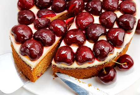 Closeup homemade cake with cherries on white wooden table.