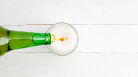 Pouring beer from bottle into glass on white wooden table. Top view. Copyspace. 스톡 콘텐츠