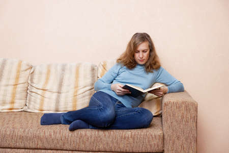 Woman sitting at home on the sofa and reading a book