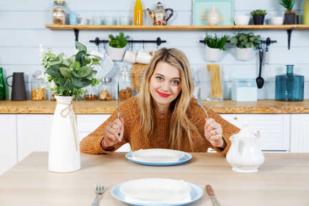 Young attractive woman sitting at table in kitchen with empty plate waiting for lunch