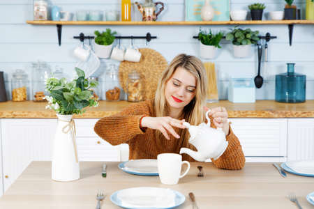 Attractive girl pours tea from a white teapot into a cup while sitting at the table in the domestic kitchen