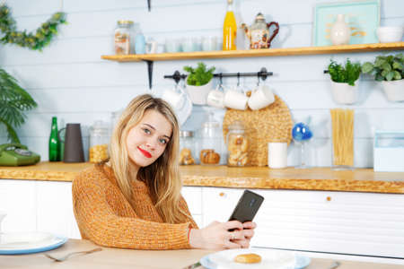Young pretty girl sitting at a table in the kitchen with a phone in her hands