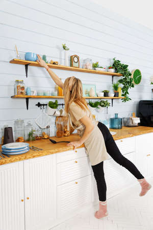 Young pretty woman reaches for a bowl on the top shelf 스톡 콘텐츠