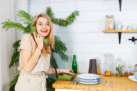 Young cheerful pretty woman talking on the old vintage phone in the kitchen 스톡 콘텐츠