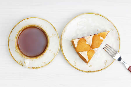 Cup of tea and piece of homemade berry pie with meringue and cookies on white wooden table. Top view. 스톡 콘텐츠