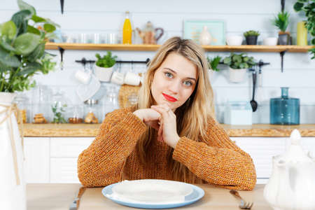 Young woman sitting at the kitchen table in front of an empty plate. Blurred background.
