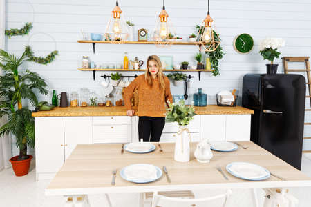 Young pretty woman stands in the home kitchen with her hands resting on the table