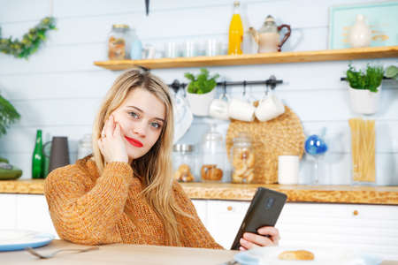Young woman sitting at the kitchen table with a phone in her hands. Blurred background.