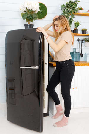 Young attractive woman open a door of a black refrigerator on the domestic kitchen. 스톡 콘텐츠