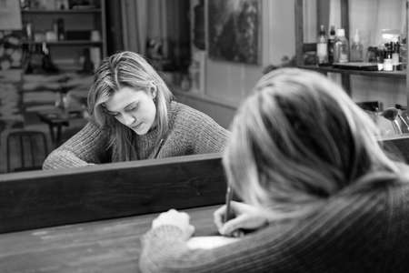 Young woman sits at a table in front of a mirror and writes something with a pen in a notebook. Shallow focus. Black and white. 스톡 콘텐츠