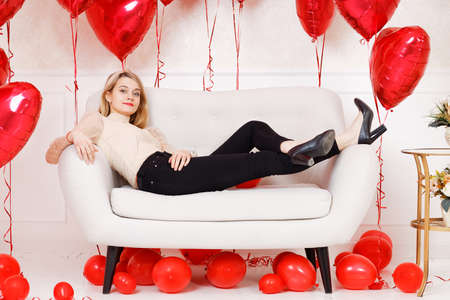 Young woman in black jeans reclining on a sofa surrounded by red balloons.