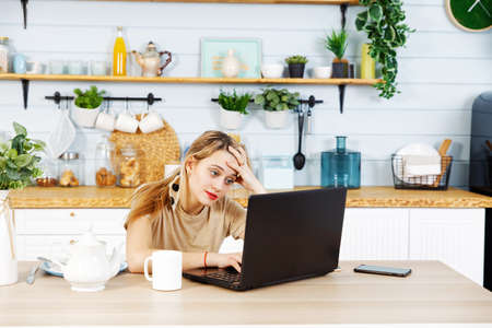 Sad and tired young woman sitting at the kitchen table in front of a laptop. Working from home concept.