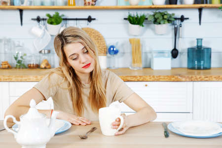 Young woman sits at the kitchen table with mug on her hand. Blurred background. 스톡 콘텐츠