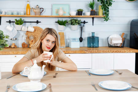 Young woman sitting at the kitchen table with a mug in her hands. Blurred background.