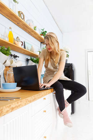 Young pretty woman in the home kitchen with laptop on the table