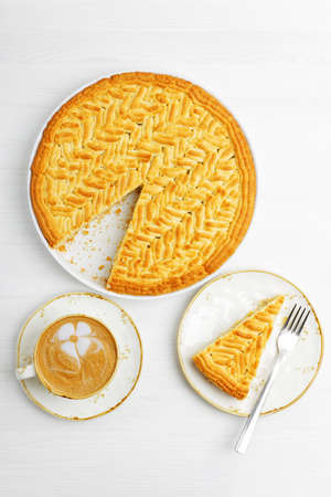 Homemade lemon pie and cup of coffee cappuccino on white wooden table. Top view.