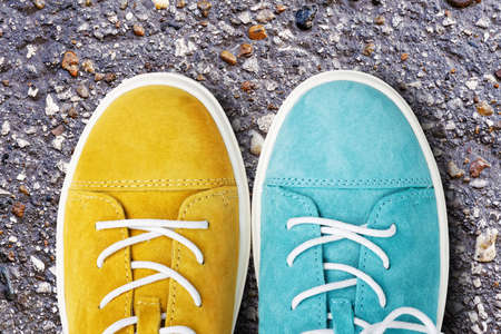 New yellow and blue suede walking shoes on asphalt road or walkway. Top view.