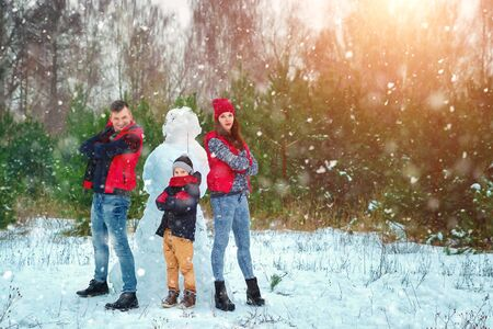 Happy family in warm clothes in the winter outdoors. Concept of holidays, holidays, winter, new year, day of grace. Family relationships, happy marriage. Stock Photo