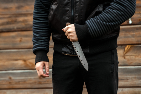 A man, a criminal in black clothes, holds a large knife in his hand. Close-up, copy space. The concept of crime, violation of the law, the criminal.
