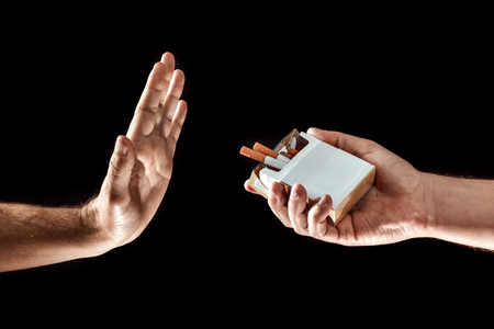 Hands close-up, stop smoking gesture, give up cigarettes, stop smoking. Creative background. The concept of smoking kills nicotine poisons. 스톡 콘텐츠 - 113387235