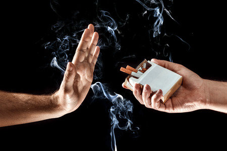 Hands close-up, stop smoking gesture, give up cigarettes, stop smoking. Creative background. The concept of smoking kills nicotine poisons.