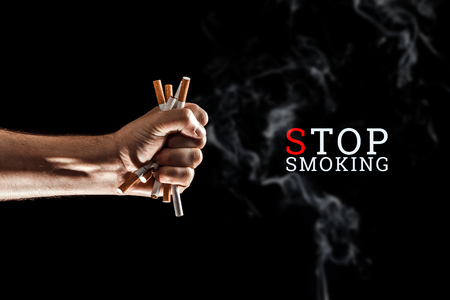 Creative background, male hand clenches a fist of a cigarette on a black background. The inscription stop smoking The concept of smoking kills, nekatin is poison, nicotine addiction. Copy space.