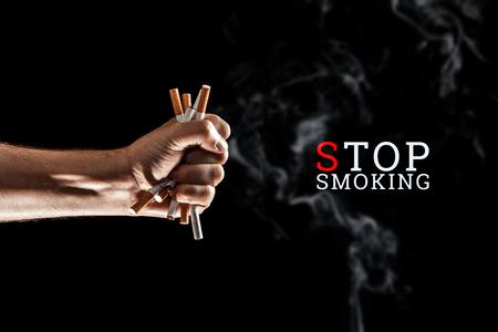 Kreativer Hintergrund, männliche Hand ballt eine Zigarette zur Faust auf schwarzem Hintergrund. Die Inschrift Rauchen aufhören Das Konzept des Rauchens tötet, Nekatin ist Gift, Nikotinsucht. Platz kopieren.