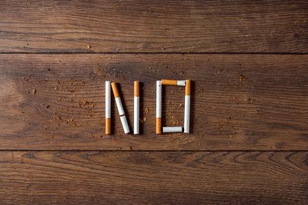 Kreativer Hintergrund, das Wort Nein besteht aus Zigaretten auf braunem Holzhintergrund. Das Konzept des Rauchens tötet Nikotingifte ab. Platz kopieren.